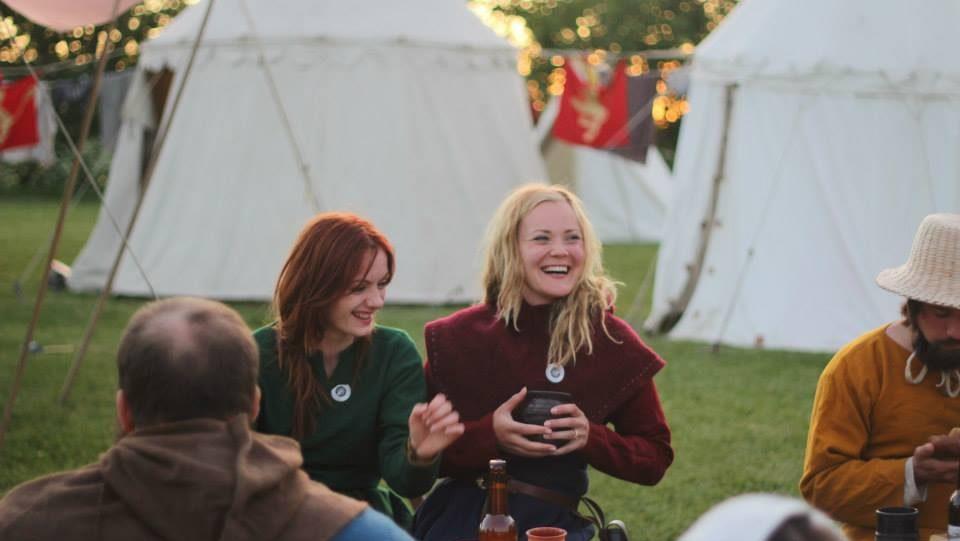 to kvinnelige medlemmer av bispeliden ler under kveldsbanketten på hamar middelalderfestival