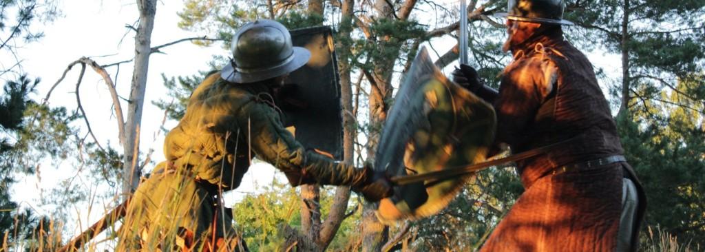 to av bispelidens medlemmer duellerer med sverd og skjold